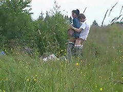 A lusty couple banging in a field