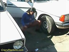 Sexual lady pissing between two parked cars