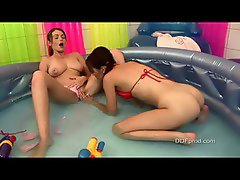 Two sizzling teens in the inflatable pool having fun together