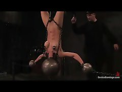 Young woman hanging upside down with her head in a bondage ball