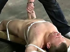 Tied up hunk gets tugged and covered in lewd wax
