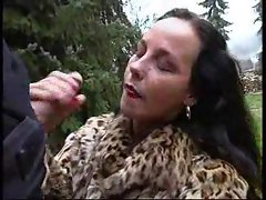 Cutie in fur coat giving handjob outdoors