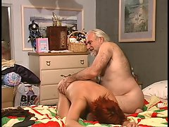 Hirsute chap spanks buxom redhead in bed