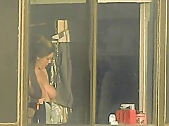 Neighbor getting dressed by the window