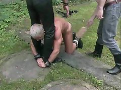 Outdoor male slave bound and whipped by a cruel Masters