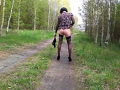 Crossdresser in sensual outfit & walking in forest near a road