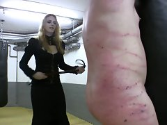 So lewd redhead mistress in leather whipping tied up slave