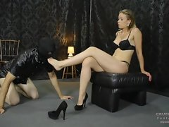 Cruel Anette's kneeling slave admires her feet and licks them passionately